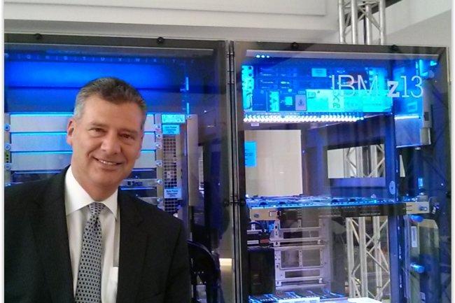 Tom Rosamilia, senior vice-président IBM Systems, pose à côté du dernier mainframe de big blue, le z13. (crédit : D.F.)