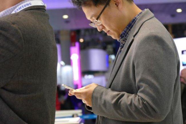 Un participant au Mobile World Congress 2016 de Barcelone avec son smartphone, le 25 février 2016. (Crédit : S.Lawson/IDGNS)