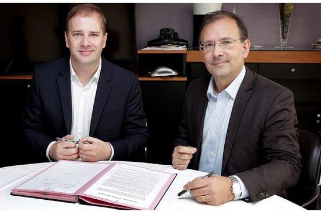 Jean-Noël Tronc (à droite), directeur général gérant de la Sacem, signe avec Silvano Sansoni, vice-président des ventes d'IBM France, le contrat de développement d'URights pour gérer les droits d'auteur. (crédit : D.R.)