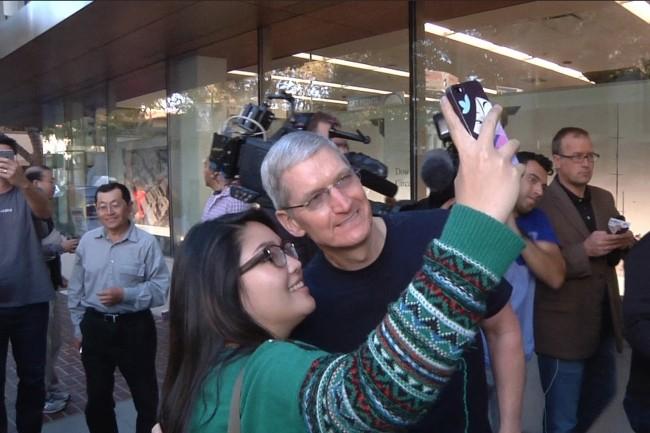 Tim Cook, CEO d'Apple, pose pour un selfie avec un client à l'extérieur de l'Apple Store de Palo Alto le 19 septembre 2014. (Crédit photo : Martyn Williams/IDGNS)