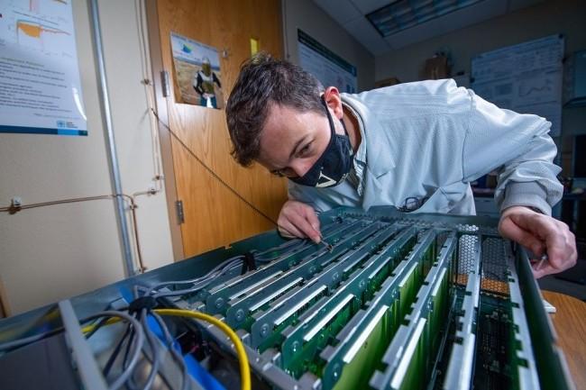 Darby Smith, chercheur au Sandia National Laboratories, effectue un premier examen des cartes informatiques contenant des neurones artificiels conçus par Intel. (Crédit: Sandia National Laboratories)